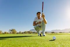 Исследование игрока в гольф зеленый цвет перед установкой съемки стоковое изображение rf
