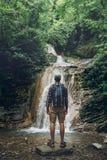 Исследователь путешественника стоит на утесе и наслаждается взглядом одичалой природы, вид сзади Пешая концепция приключения Стоковое Фото