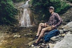 Исследователь путешественника с рюкзаком сидит на реке и наслаждается концепцией приключения окружающего взгляда исследуя пешей Стоковые Изображения RF