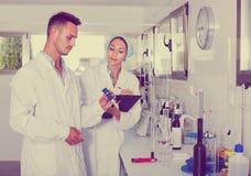 2 исследователя в белом пальто проверяя кислотность вина в laborator Стоковая Фотография RF