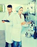 2 исследователя в белом пальто проверяя кислотность вина в laborator Стоковое Изображение