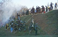 Историческая реконструкция сражения - атакующие бежать вверх холм против защитников стоковая фотография