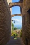 Историческая улица Assisi с взглядами умбрийской сельской местности стоковые фото