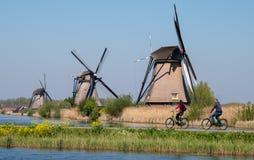 Исторические ветрянки с велосипедистами задействуя вдоль стороны канала на переднем плане, на Kinderdijk, Голландию стоковое изображение rf