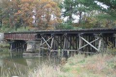 Исторический, выдержанный мост рельса над водой Стоковая Фотография RF