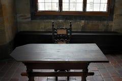 Исторический интерьер с деревянной мебелью, декоративным потолком, деревянным полом, картинами на стенах и окнами на средневеково стоковая фотография