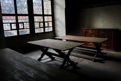 Исторический интерьер с деревянной мебелью, декоративным потолком, деревянным полом, картинами на стенах и окнами на средневеково стоковое фото rf