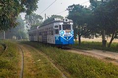 Исторический трамвай Калькутты двигает через зону Kolkata Maidan на туманном утре зимы Стоковые Фотографии RF
