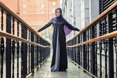 Исламская красивая женщина в мусульманском платье стоя на европейской улице Стоковая Фотография RF