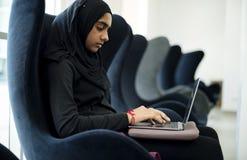 Исламское усаживание девушки и компьтер-книжка использования Стоковые Изображения