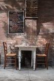 Италия, болонья, таблица и стулья харчевни Стоковая Фотография