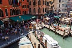 ИТАЛИЯ, ВЕНЕЦИЯ - ИЮЛЬ 2012: Толпа туристского близко грандиозного канала 16-ого июля 2012 в Венеции. Больше чем 20 миллионов тури Стоковая Фотография RF