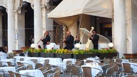Италия venice Оркестр который играет около таблиц баров аркады Сан Marco стоковые изображения