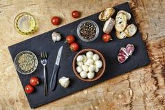Итальянская еда, bruschettas, ингридиенты моццареллы сыра, специи, варя, базилик, чеснок черная доска, деревенский стиль, copyspa Стоковые Фотографии RF