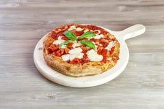 Итальянская изысканная пицца на деревянной прерывая доске стоковое фото