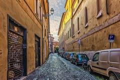 Итальянская улица с гаражами фасада, цветочными горшками и яркими зданиями стоковое изображение
