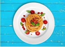 Итальянские макаронные изделия с томатами на деревянной предпосылке Стоковое Изображение