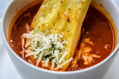 Итальянский суп минестроне с хлебом чеснока и заскрежетанным сыром чеддера Стоковое фото RF