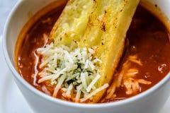Итальянский суп минестроне с хлебом чеснока и заскрежетанным сыром чеддера Стоковая Фотография RF