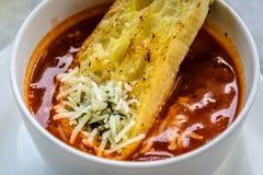 Итальянский суп минестроне с хлебом чеснока и заскрежетанным сыром чеддера Стоковые Фото