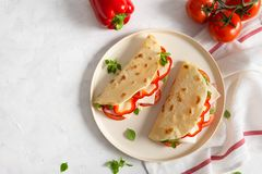 Итальянский flatbread romagnola piadina с красным перцем, томатами, ветчиной ветчины, сыром и базиликом на плите на белое деревян стоковые изображения