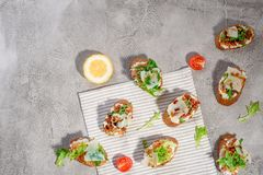 Итальянское bruschetta с семгами, томатами, сыром и pesto базилика на серой конкретной или каменной предпосылке стоковое фото rf