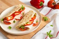 Итальянское piadina на белой плите с томатами и перцем овощей на белой предпосылке E Взгляд со стороны, космос экземпляра стоковое фото