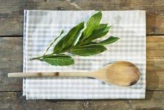 Италия, Тоскана, Magliano, деревянная ложка, листья залива и салфетка на деревянном столе Стоковая Фотография RF