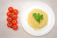 Итальянская еда: макаронные изделия на большой белой плите рядом с красными томатами вишни и зелеными оливками Стоковая Фотография RF