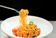 Итальянская женщина еды есть спагетти с вилкой в белой плите Стоковые Фотографии RF