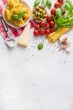 Итальянская кухня и ингридиенты еды на белой конкретной таблице Сыр пармесан томатов оливкового масла оливок Tagliatelle спагетти стоковое изображение
