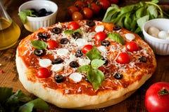 Итальянская пицца с базиликом, моццареллой и томатами стоковые фотографии rf