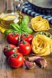 Итальянские и среднеземноморские пищевые ингредиенты на деревянной предпосылке Макаронные изделия томатов вишни, листья базилика  Стоковые Изображения