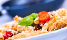 Итальянские макаронные изделия с томатным соусом и сыром как базилик зеленого цвета украшения выходят Стоковое фото RF