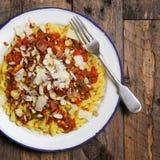 Итальянские макаронные изделия с томатным соусом, копченым pancetta, зажаренной в духовке миндалиной стоковая фотография