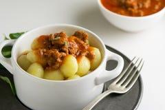 Итальянский рецепт: gnocchi картошки сделанный дома с томатным соусом b Стоковое Фото