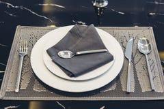 Итальянский современный модельный дом: Белая плита и голубая салфетка с комплектом Dinning серебряной ложки, вилки и ножа Стоковые Фотографии RF