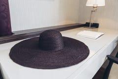 Итальянский современный модельный дом: Сплетя шляпа на таблице в рабочей зоне Стоковые Изображения