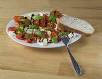 Итальянский caprese салат на белом базилике томатов плиты mozzarel Стоковая Фотография