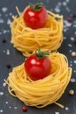 Итальянское гнездо с томатами вишни, конец-вверх макаронных изделий яичка Стоковое фото RF