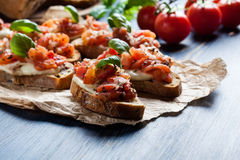 Итальянское bruschetta с зажаренными в духовке томатами, сыром моццареллы и Стоковое Фото