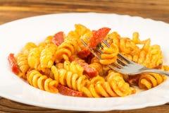 Итальянское fusilli макаронных изделий при томатный соус и сосиска skewered на вилке в плите, конце-вверх, селективном фокусе стоковое изображение rf