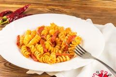 Итальянское fusilli макаронных изделий при томатный соус и сосиска skewered на вилке в плите, конце-вверх, селективном фокусе стоковые изображения