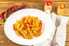 Итальянское fusilli макаронных изделий с томатным соусом и сосиской в плите, салфетке, вилке, перце на деревянном столе стоковое изображение rf