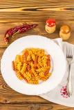 Итальянское fusilli макаронных изделий с томатным соусом и сосиской в плите, салфетке, вилке, перце на деревянном столе, взгляд с Стоковая Фотография RF