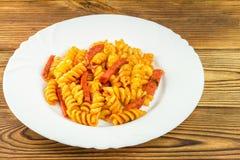 Итальянское fusilli макаронных изделий с томатным соусом и сосиской в плите на деревянном столе Стоковые Фото