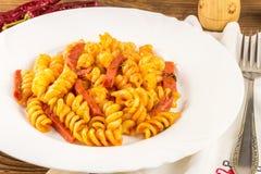 Итальянское fusilli макаронных изделий с томатным соусом и сосиской в плите, салфетке, вилке на деревянном столе стоковые изображения