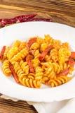 Итальянское fusilli макаронных изделий с томатным соусом и сосиской в плите, салфетке, перце на деревянном столе стоковое изображение rf