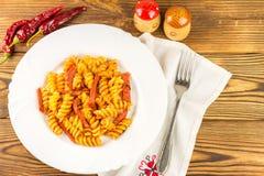 Итальянское fusilli макаронных изделий с томатным соусом и сосиской в плите, салфетке, вилке, перце на деревянном столе, взгляд с стоковое фото