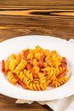 Итальянское fusilli макаронных изделий с томатным соусом и сосиской в плите, салфетке на деревянном столе стоковые фото